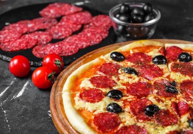 Pizza al salame con olive su una superficie scura