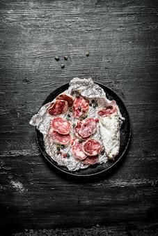 Fette di salame su un foglio in padella con spezie sulla lavagna nera.