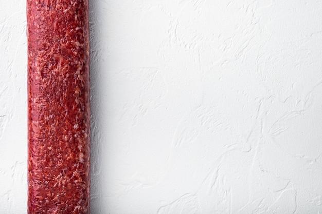 Set di salsiccia affumicata salame, su tavolo in pietra bianca, vista dall'alto piatta