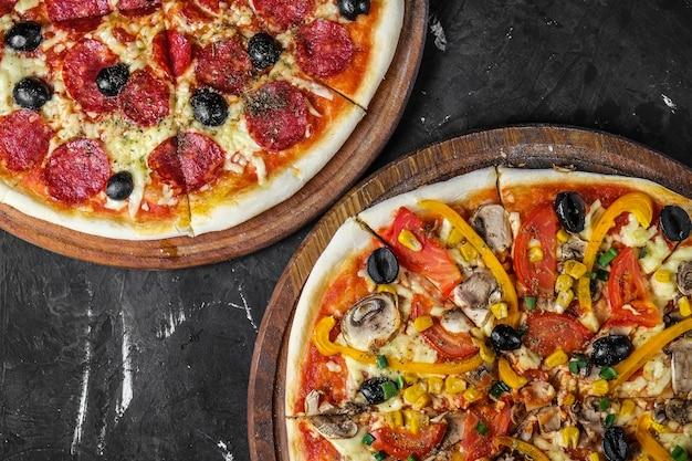 Salame e pizza vegetariana su una superficie scura