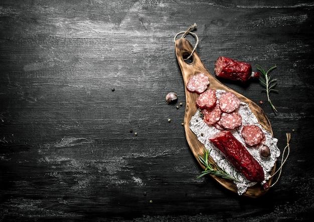 Salame con rosmarino fresco e spezie sulla tavola rustica nera.