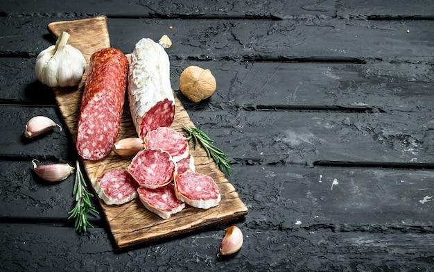 Salame con aglio e rosmarino sulla tavola rustica nera.
