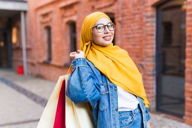 Concetto di acquisto e vendita - ragazza musulmana araba felice con le borse della spesa dopo il centro commerciale