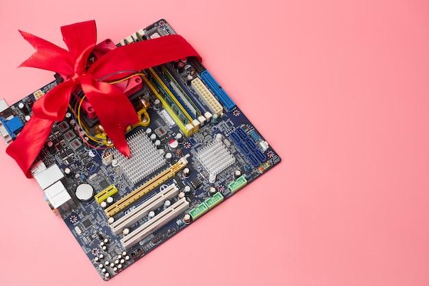 Vendita di componenti per computer, scheda madre in nastro rosso, su sfondo rosa, banner, copia dello spazio