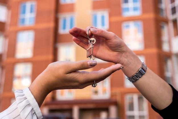 Concetto di vendita che consegna le chiavi al nuovo proprietario sullo sfondo dello sfondo della zona residenziale