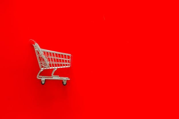 Concetto di vendita con carrello della spesa su sfondo rosso