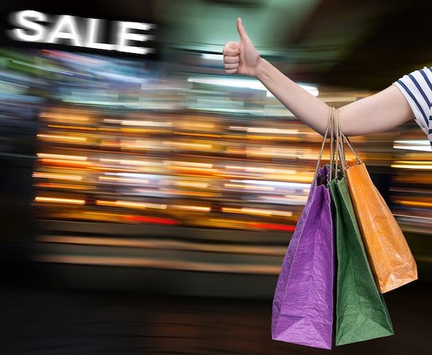 Vendita. mano con le borse della spesa contro il centro commerciale sfocato sullo sfondo con copia-spazio