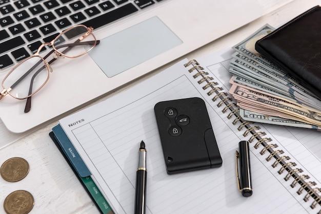 Chiavi della macchina di concetto di acquisto in linea di vendita con banconote del dollaro sopra il primo piano della tastiera del computer portatile