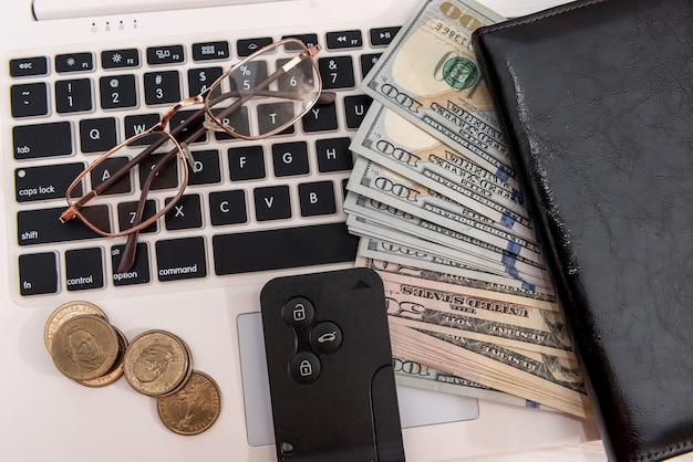 Chiavi della macchina di concetto di acquisto online di vendita con le banconote del dollaro sopra il primo piano della tastiera del computer portatile