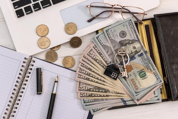 Chiavi di casa di concetto di vendita o affitto con banconote da un dollaro e laptop, risparmiando