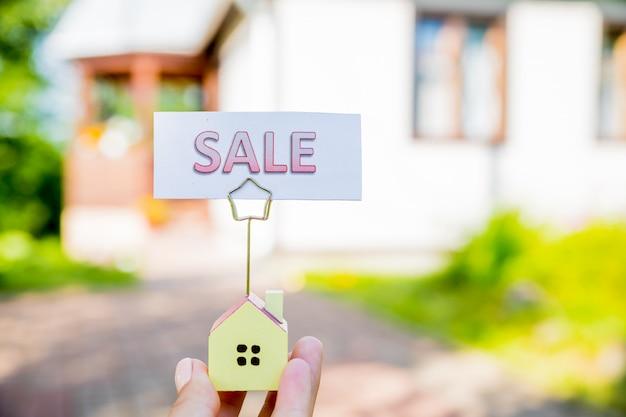 Segno di vendita con la casa del piccolo modello - concetto d'acquisto del bene immobile