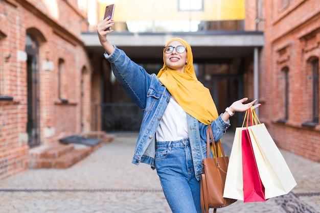 Vendita, tecnologie e concetto di acquisto - donna musulmana araba felice che prende selfie all'aperto dopo