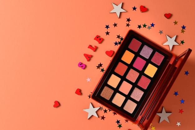 Testo di vendita su uno sfondo arancione. prodotti per il trucco professionale alla moda con prodotti cosmetici di bellezza, ombretti, ciglia, pennelli e strumenti.