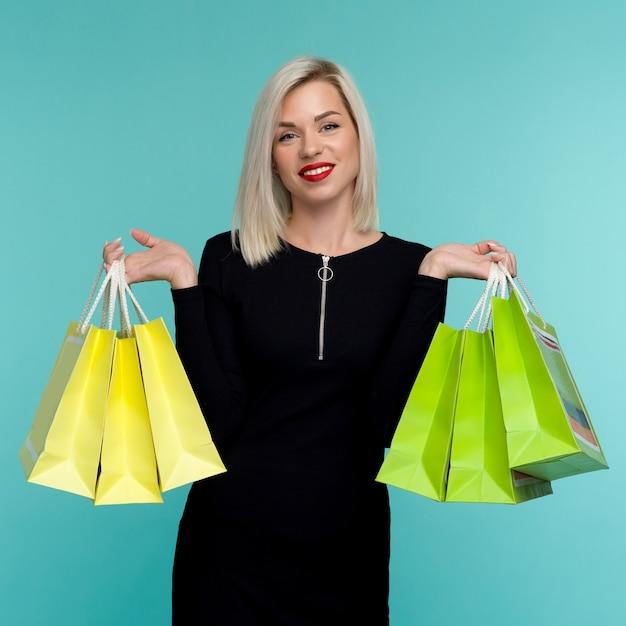 Vendita giovane donna sorridente che tiene i sacchetti della spesa in venerdì nero
