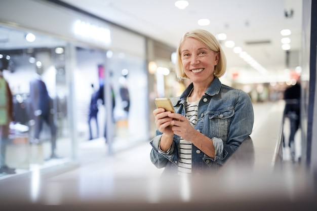 Consulente di vendita del negozio di abbigliamento che manda un sms durante la pausa