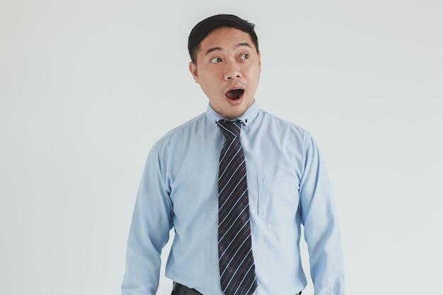 L'addetto alle vendite che indossa una camicia blu e una cravatta scioccato sembra uno spazio vuoto per la pubblicità