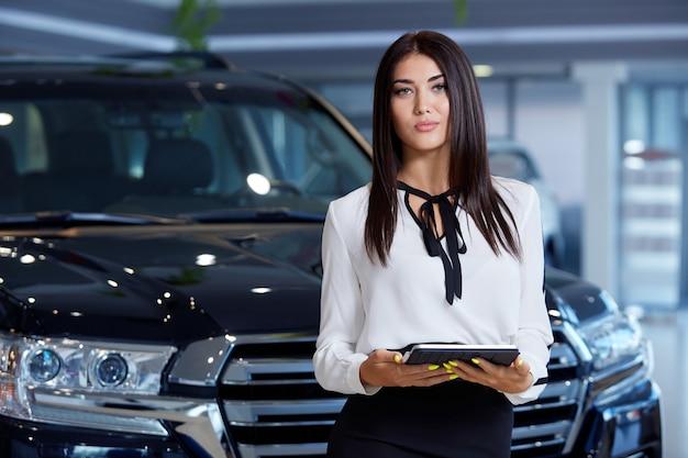 Una ragazza responsabile delle vendite in una concessionaria di auto con un tablet in mano sullo sfondo delle automobili