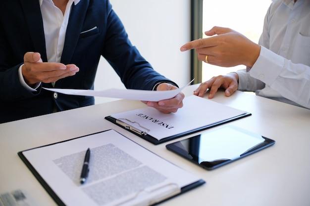 Responsabile commerciale che dà documento di domanda di richiesta di consulenza, considerando l'offerta di prestito ipotecario per l'assicurazione auto e casa.