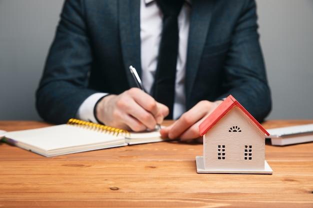 Responsabile vendite o agente immobiliare con dettaglio le condizioni di acquisto di una casa con promozioni assicurative