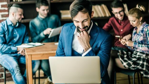 Responsabile delle vendite con un laptop e un team aziendale che discute dei problemi attuali dell'azienda