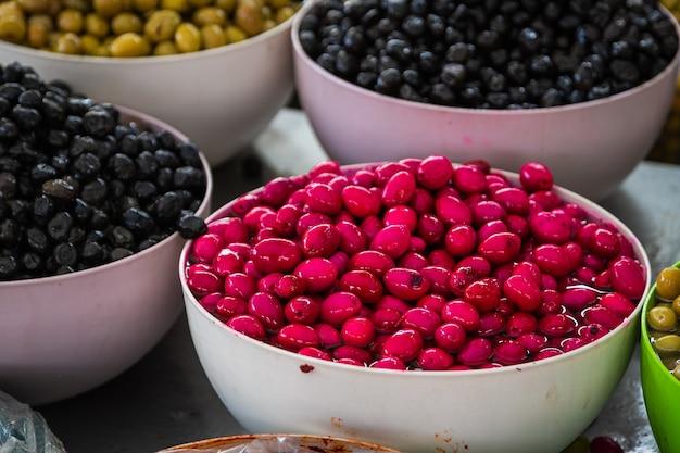 Vendita di prodotti tradizionali olive mediterranee al mercato tante ciotole di olive nere rosa e verdi al mercato contadino