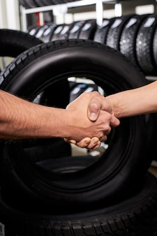 Venditore e cliente si stringono la mano nel negozio di servizi auto, scelta fatta di sesso maschile, acquisto di pneumatici per auto per l'inverno