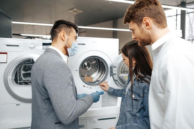 Il venditore in un ipermercato che indossa una maschera medica mostra ai suoi clienti una nuova lavatrice