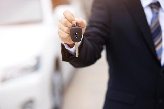 Il venditore consegna le chiavi della nuova macchina al cliente nello showroom.
