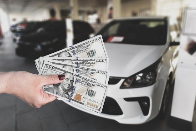 Venditore che vende auto in un negozio di auto o uomo d'affari che acquista una nuova auto con un dollaro in mano.