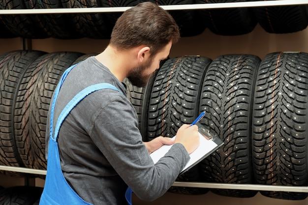 Venditore con appunti vicino a pneumatici nel negozio di automobili