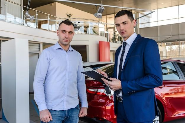 Venditore che lavora con il cliente nello showroom, operazione di acquisto auto
