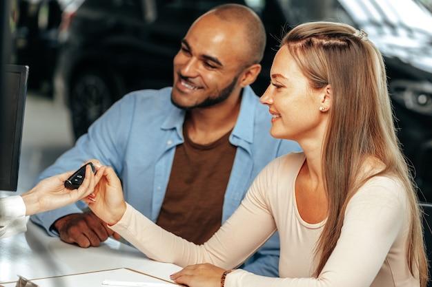 Addetto alle vendite che dà la chiave all'acquirente in un salone di automobile