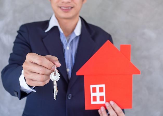 Il commesso è pronto ad accogliere le vendite di case in mano, consegnando le chiavi di casa e i disegni della casa rossa. concetto di mutuo