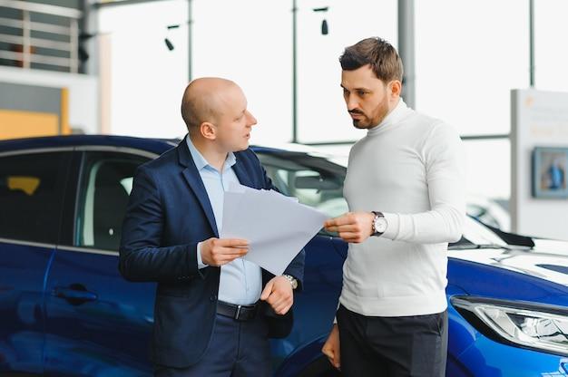 Addetto alle vendite che vende automobili in concessionaria auto