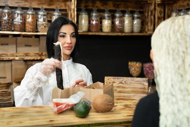 Commessa confeziona una borsa della spesa con merci in un negozio di alimenti naturali.