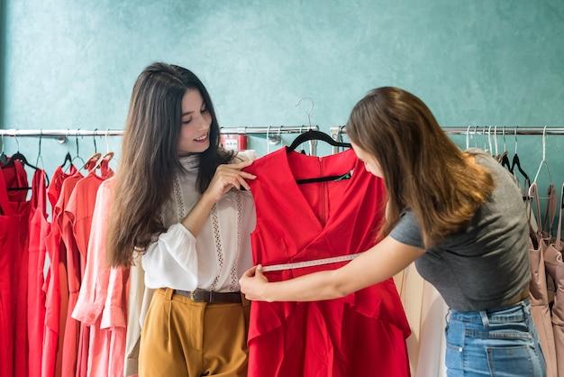 Commessa lavora con il cliente nel negozio di moda. concetto di fashion design. venerdì nero