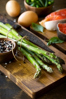 Asparagi e uova di salmone su fondo di legno spazio libero per il tuo testo