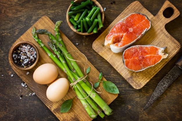 Asparagi di salmone e uova su fondo di legno vista dall'alto piatta spazio libero per il testo