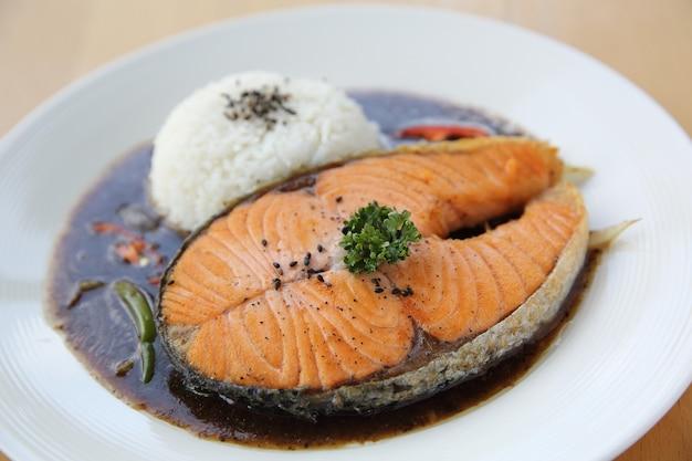 Carta salmone nero con riso su fondo legno
