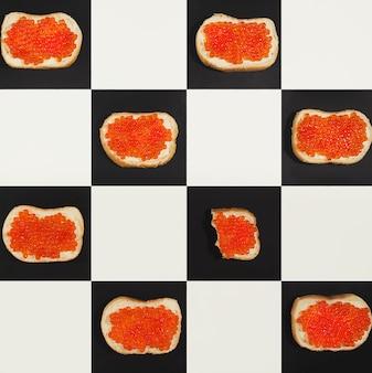 Modello di tartine di caviale di salmone su bordi di scacchi