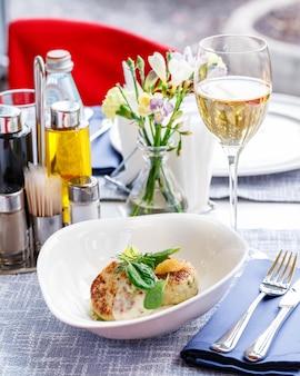 Cotolette di salmone e baccalà con spinaci e caviale di luccio con salsa bianca in un ristorante che serve