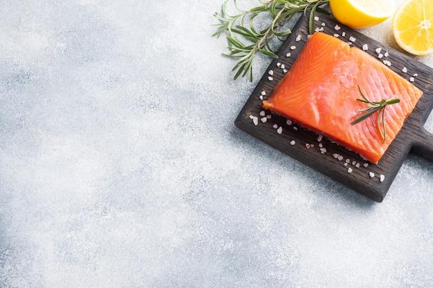 Filetto di salmone, pesce salato rosso su un tagliere di legno.