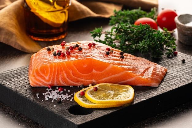 Bistecca di filetto di salmone e condimento sul tagliere di legno scuro sul tavolo marrone