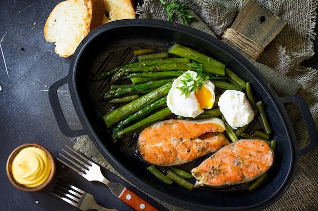 Trancio di salmone alla griglia con uovo in camicia di asparagi in padella vista dall'alto