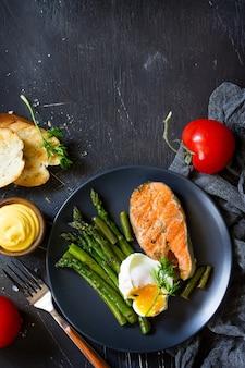 Bistecca di pesce di salmone alla griglia con uovo in camicia di asparagi vista dall'alto piatta spazio libero per il testo