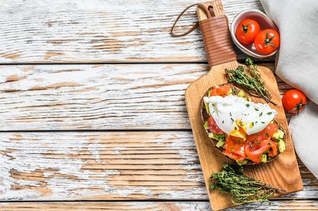 Salmone e uovo in camicia su pane tostato alla griglia