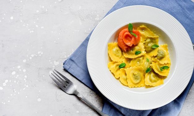 Alimento italiano tradizionale dei ravioli di color salmone con basilico fresco in un piatto bianco su una tavola di pietra grigia. ricetta cibo italiano. cibo piatto disteso