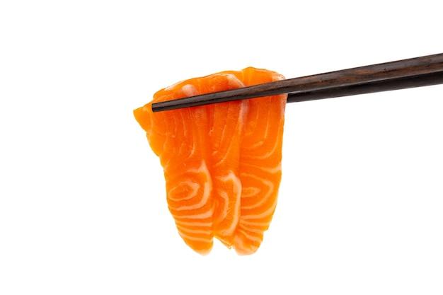 Sashimi crudo di salmone con bacchette su sfondo bianco