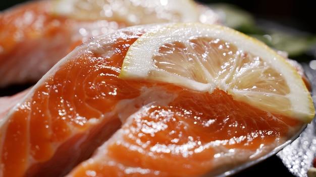 Trancio di pesce rosso di trota cruda di salmone con erbe e limone e olio d'oliva ruotato su ardesia
