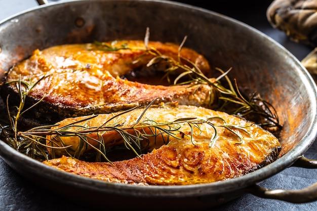 Salmone arrosto bistecche rosmarino sal pepe olio d'oliva - close-up. Foto Premium